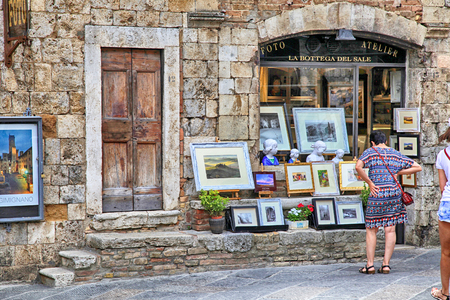 shop window: SAN GIMIGNANO, ITALY - JULY 22, 2017 : Tourists in the gift shop at the medieval town of San Gimignano, Siena, Tuscany, Italy