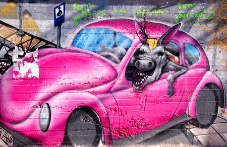 CRETE, GREECE - JULY 24, 2016: Colorful graffiti urban art with fun car and jackass on the street walls