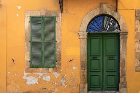 old green door and window of ancient european yellow building, Cyprus Imagens