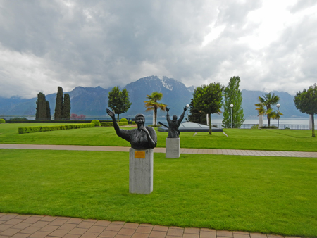 MONTREUX, SWITZERLAND - MAY 09, 2013: Landscape with Alps, lake Geneva and statue to Aretha Franklin, designed by Italian artist Marco Zeno, stands in the garden of the Montreux Palace in Montreux, Switzerland