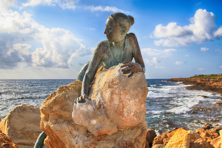 PAPHOS, CYPRUS - JANUARY 12, 2018: A bronze statue of woman called Sol Alter by Yiota Ioannidou on a stone located on sea promenade, Paphos, Cyprus. Stock Photo