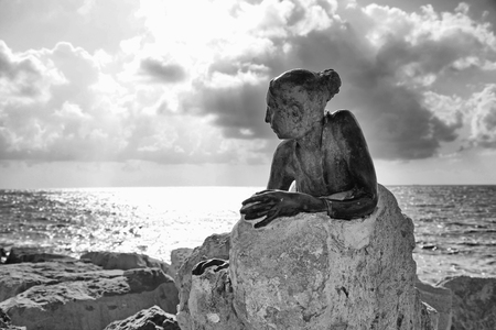 PAPHOS, CYPRUS - JANUARY 12, 2018: A bronze statue of woman called Sol Alter by Yiota Ioannidou on a stone located on sea promenade, Paphos, Cyprus. Black and white image