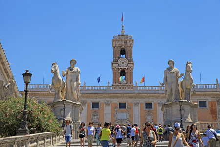 ROME, ITALY - JULY 17, 2017: Tourists on Michelangelo stairs to Piazza del Campidoglio on the top of Capitoline Hill and Palazzo Senatorio (Senatorial Palace), Rome, Italy. Capitol Hill - one of the hills of ancient Rome, where in ancient times was the Se