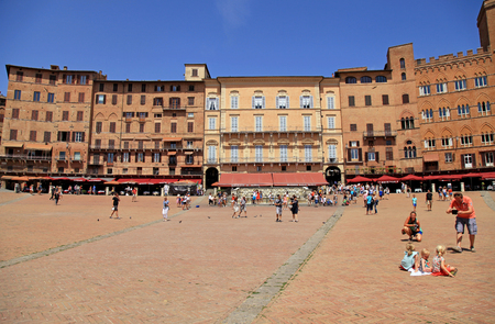 SIENA, ITALY - JULY 21, 2017: Tourists on Piazza del Campo town square surrounded by historical buildings in Siena, Italy.