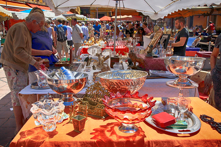 NICE, FRANCE - MAY 13, 2013: Tourists and local people buy old goods at famous antique market The Cours Saleya at Nice, French Riviera, France Editoriali