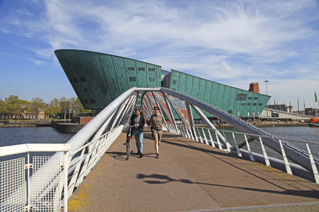 AMSTERDAM,NETHERLANDS - MAY 6, 2016: People walking on the modern bridge near the Nemo museum in Amsterdam, Netherlands. Science Center NEMO designed by Renzo Piano- largest childrens science educational museum, knowledge institute and center of tourism i Editorial