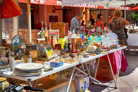 NICE, FRANCE - MAY 13,2013: Market stall at the famous antique market Cours Saleya every Monday in Nice, French Riviera, France. Huge variety of collectibles is on offer: silver, crystal,ceramics, paintings,etc