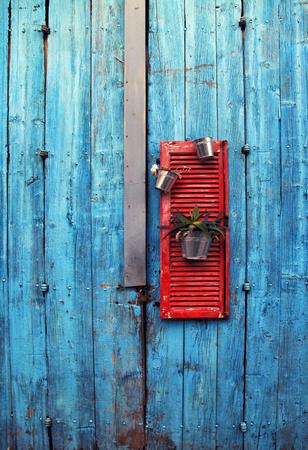 flower pots on red wooden shutter on an grange blue wall background 写真素材