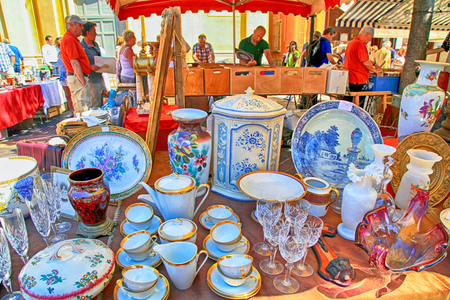 NICE, FRANCE - MAY 13,2013: Market stall at the famous antique market Cours Saleya in Nice, French Riviera, France. Huge variety of collectibles is on offer: silver, crystal,ceramics, paintings,etc
