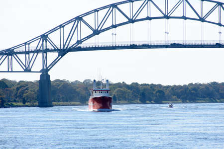 Commercial fishing vessel passing under the Bourne Bridge while traveling through the Cape Cod Canal. Stock Photo