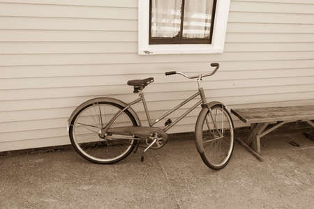 Black and whit sepia of a vintage bicycle leaning against the wall of a building under a window next to a wood bench. Stock fotó