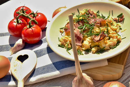 Fresh home-made breakfast eggs, onion and fried ham, set on a wooden table Stock Photo