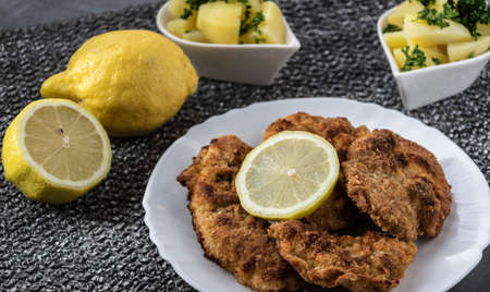 Pork schnitzel with lemon and diced potatoes Stock Photo
