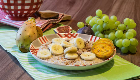 Delicious oatmeal with chocolate and pieces of fruit made of figs, bananas, grapes and cacti figs