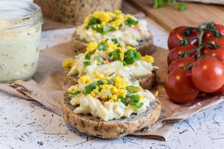 caes: extensión de huevo sobre pan casero fresco redondo, decorado con cebolleta y yema machacada