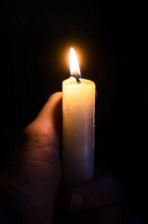 Kerze in der Hand auf schwarzem Hintergrund mit klarem Docht Standard-Bild
