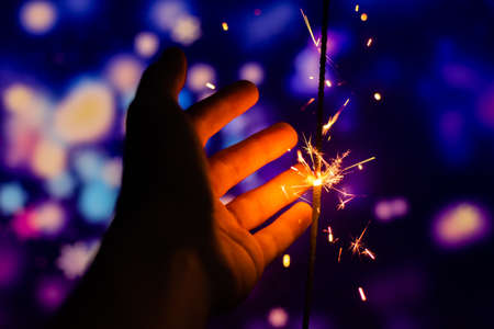 Photos on a bright blue purple background with sparklers festive lights holiday and Christmas and New Year on the desktop or banner on the website