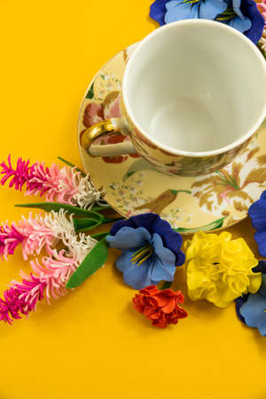 A series of photographs with beautiful compositions on a yellow background on the theme of relaxation, tea drinking, cozy still lifes with flowers and a decorative set, a cup and saucer Foto de archivo
