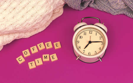 Coffee time morning concept, old vintage alarm clock on purple retro background, knitted sweaters photo