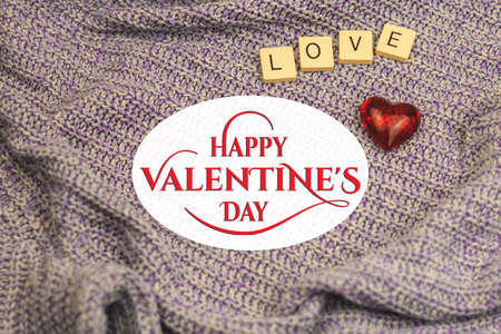 Happy Valentine's Day greeting card with text and logo, postcard or poster, love word and one red heart on knitted background photo Stock fotó