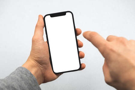 Mockup with mobile phone and man hands, person is touching white blank screen