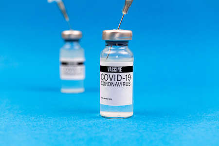 Coronavirus vaccine vials in hospital laboratory on a blue background, medical research concept photo