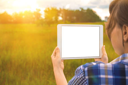 Planning for the building land, young girl holds tablet screen mockup next to field at sunset, nature background, copy space photo