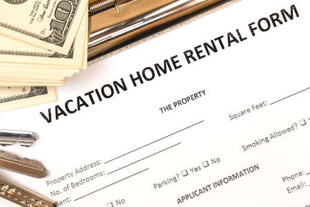Mortgage and rental housing real estate application form. Vacation concept. House keys, money, top view Stock Photo