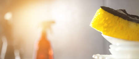 Kitchen housework banner design, copy space, unwashed dirty dishes with yellow sponge on it, background of spray bottle, selective focus Stock Photo