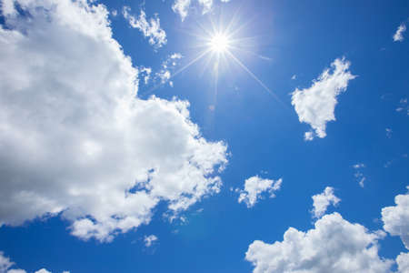 Sunny background, blue sky with white clouds and sun.Light from the sun touches the camera lens.The impact on photos is called Lens Flare. Stock Photo