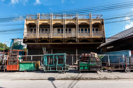 Old building with tricycle Used to store in front of the building on a bright sky.