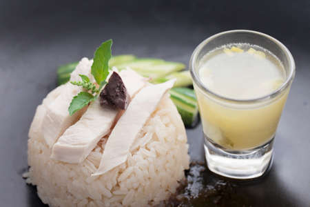 Hainanese chicken rice or steam chicken rice with sauce on dark background.Khao Man Gai Recipe . Thai Street Food Style Stock Photo