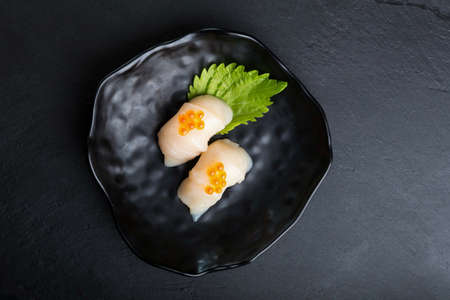 Creative Japanese food.Scallop Sushi on oba  leaf.Salmon roe is top