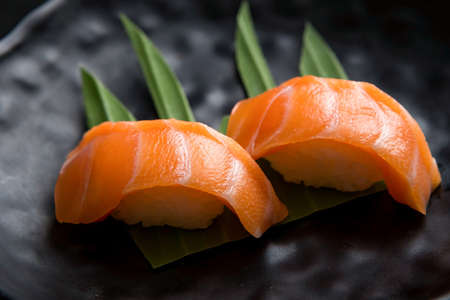 Japanese food .salmon sushi on a black plate, separate on a black background, view from a high angle 免版税图像
