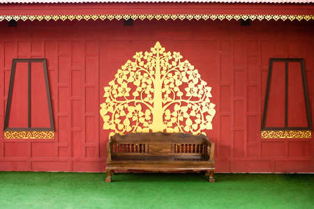 Wooden chairs on artificial grass With a beautiful golden red wall 免版税图像