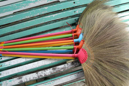 wooden chair: Colorful of plastic broom on the old wooden chair.