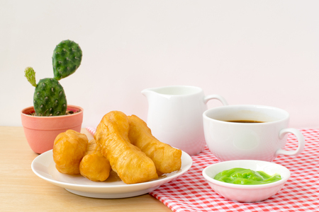 patongkoh: Chinese dessert ; deep fried dough stick with cute spoon and fork with milk and a cup of coffee on the table