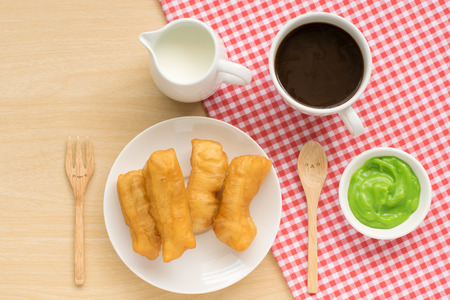 patongkoh: Top view of chinese dessert ; deep fried dough stick with cute spoon and fork with milk and a cup of coffee on wooden background
