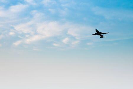 Silhouet vliegtuig op de blauwe lucht met wolken
