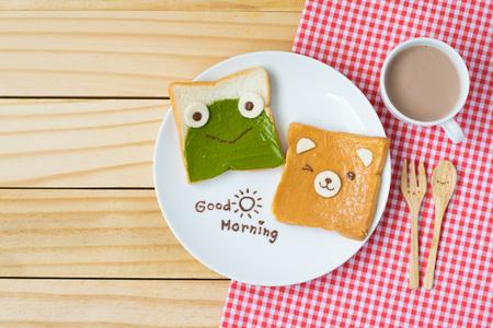 bovenaanzicht van schattig ontbijt voor kinderen, groene thee verspreid en pindakaas ontwerp aan kikker en beer op brood met tekst van de goedemorgen en een kopje cacao met schattige lepel en vork op houten achtergrond