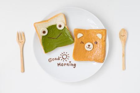 bovenaanzicht van schattig ontbijt voor kinderen, groene thee verspreid en pindakaas ontwerp aan kikker en beer op brood met goedemorgen tekst met schattige lepel en vork op witte achtergrond Stockfoto