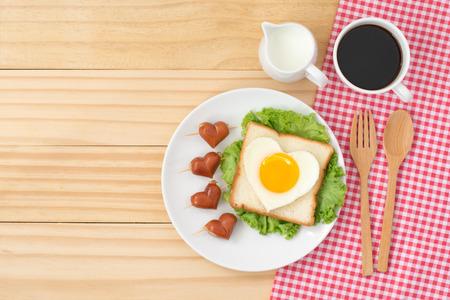 Ontbijt, bovenaanzicht van schattig eten, hartvorm gebakken ei op brood en groente met hartvorm worsten dienen met een kopje koffie en melk op houten achtergrond Stockfoto