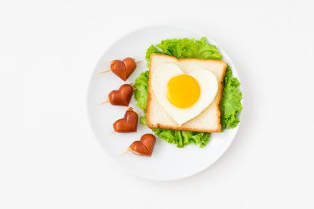 Het ontbijt, hoogste mening van leuk voedsel, hartvorm braadde ei op brood en groente met de worsten van de hartvorm op geïsoleerde witte achtergrond Stockfoto