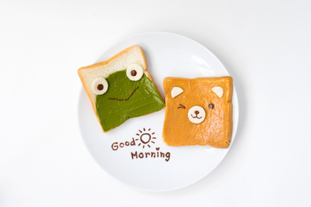 Top view of cute breakfast for kids, green tea spread and peanut butter design to frog and bear on breads with good morning text on white background