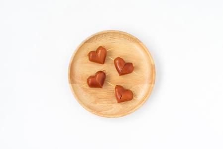 Ontbijt, bovenaanzicht van schattig eten, hartvorm worstjes op houten schotel op geïsoleerde witte achtergrond Stockfoto
