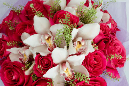 Bouquet with pink roses, orchids and colorful cymbidium in the box.