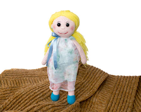 knitted cute baby girl doll with yellow hairs stands on the brown scarf isolated on white