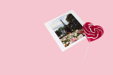 Lollipop with heart shape with romantic postcard on pink background. Archivio Fotografico