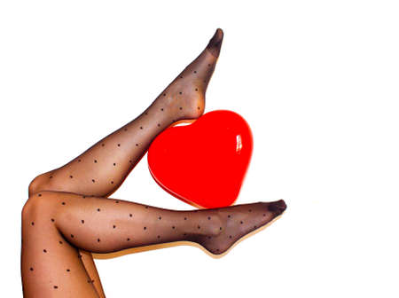 womens legs in black tights holding red heart ballon on the white background