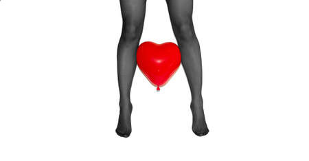 woman legs in black tights with red heart baloon between on white background Stock Photo